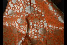 Ceci est une belle Banarasi pur brocart de soie tissu motif floral en orange et d'or. Le tissu illustrent petites fleurs tissées d'or sur fond orange. Vous pouvez utiliser ce tissu pour faire des...
