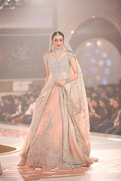 Taking us back to the mughal era, Asifa and Nabeel's collection was all about royal colors, classic hues, opulent fabrics and rich embroideries. While keeping the tradition alive, the label also pl… | pakistan bridal couture week | peach double shirt / anarkali with silver blouse and peach dupatta | nikah or walima dress