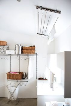 Organized Laundry Room  Shelves and baskets add order and function.  A modular wall-mounted system allows for expanding storage needs in this airy laundry room. A ceiling drying rack eliminates the need for an electric dryer and saves valuable energy. House and Home.com