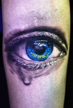 Beautiful photo realistic blue eye tattoo.