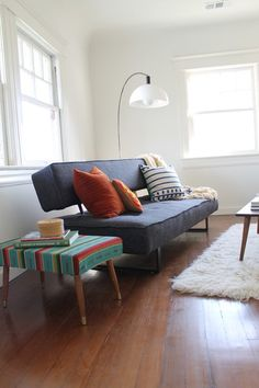 Mexican blankets can also be used as one might use upholstery fabric. A vintage ottoman covered with an aqua striped version gives this living room a retro ethnic touch.