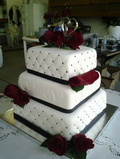 Top and bottom tier are white fondant quilted with black dots and middle tier is white fondant with interlocking hearts to match the topper