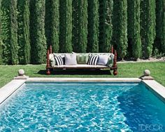 Grey's Anatomy star Ellen Pompeo worked with interior designer Martyn Lawrence-Bullard to create a Mediterranean-style setting at her family's home in the Hollywood Hills. Cypress trees, a common sight along the French Riviera, line the pool area; the outdoor sofa was designed by Lawrence-Bullard.    www.facebook.com/...