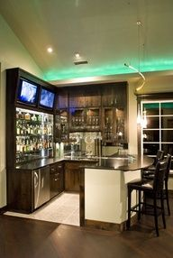 For the den upstairs by the fireplace....Bar equipped with two tvs and bar stools! :)  How awesome would it be to have this in your house?!?