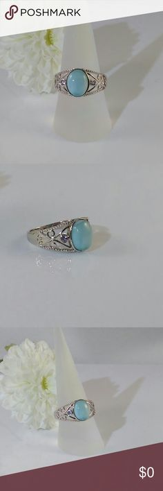 Genuine Larimar and Tanzanite Ring Beautiful and serene, Caribbean blue larimar. The 3.1 carat, 8x10mm oval larimar cabochon gemstone is accented with two 2mm, round cut genuine tanzanites that are 0.1 carat tw. This fancy filigree sterling silver size 8 ring is rhodium plated for a superior finish. New.  Measurements and weights are approximate. Photos may be enlarged to show detail. Jewelry Rings
