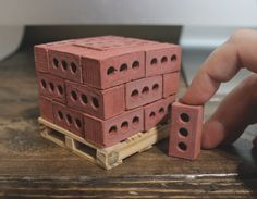 """Carefully stacked 1:6 scale red bricks on a pine wood pallet secured with real nails. Each red brick measures 1.33"""" x .66"""" x .66""""."""