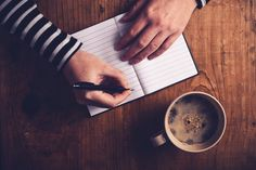 Woman drinking coffee and writing a diary note - Woman drinking coffee and making a diary note, top view of female hands writing in notebook, retro toned image with selective focus.