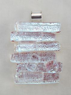 This beautiful dichroic glass pendant is fused of strips of silver dichroic glass and top layer of clear glass. The top layer gives the pendant