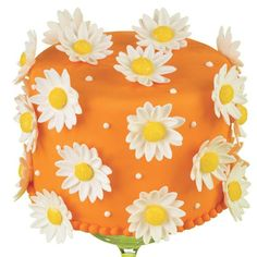 A Burst of Daisies Cake. 3-D daisies pops on a field of orange fondant. A sunshiny cake that's so perfect for showers, mother's day, birthdays and so many more special occasions. #wilton #cake #cakedecorating #dessert