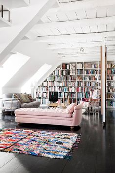 Fresh shabby-chic library/reading area with white exposed beams, vintage furniture (look at that pink chaise lounge!), and plenty of natural lighting. Me likey.