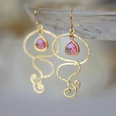 Romantic and elegant earrings featuring matte golden hammered pendants and glass drops in fresh rosy pink color. These pink drops are faceted and are