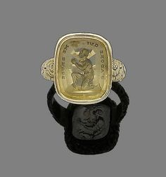A late 18th century citrine intaglio ring The citrine plaque carved to depict an African slave kneeling to the sun, with the inscription 'J'adore qui me brule' (I love he who burns me), to a gold floral engraved band and mount,
