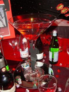 www.la-occasion.com - James Bond Themed Party Maritini Vase with Red Stones, Clear Water and Black Fish. Black Straw placed in vase with 007 logo in Glitter Gold and Red. Base of the vase, small spy men cutout