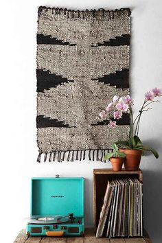 Beautiful textured rug on the wall, crate, and best of all - an orchid!