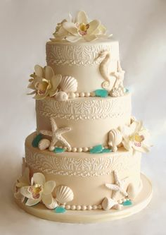 beach wedding cake.  This three tier cake was covered in ombre beige fondant. The band at top of each tier caw done with royal icing using a custom made stencil to match the wedding invites. Orchids and seashells were made in gumpaste, and for the sea glass isomalt was used.