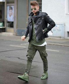 Jaquetas estilo motoqueiro são um charme. Na foto: Jaqueta preta, camiseta básica verde, calça cargo verde e tênis verde.