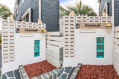 玄関前のデザインウォールも自然を感じさせてくれる工夫でいっぱい。海の青をイメージした3連のガラスブロックは訪れる人の目を楽しませてくれます。門灯として取り付けたマリンライトとの相性も抜群です。デザインウォール前に設けた植栽スペースには鮮やかな色味のレンガチップを敷き詰め、大地の力強さを表現しました。