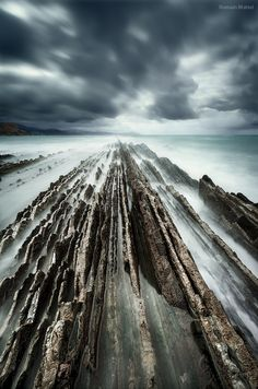 If you're interested to see Behind the Scenes and Before/Afters, follow me on my  Facebook Page  This is the beautiful beach of Zumaia in the Spanish Basque country where geographical stratas sunk literally in the sea forming a structure called flysch. I got really wet during this tiring photo session where I had to clean the filters and recompose every minute because I had to pull the camera out of the splashing waves. But I think it was worth it :) Technically, this is a manual blending of…