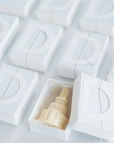 "A miniature white-chocolate cake, in a white box with a handmade ""D,"" cut out from ivory paper, on the lid, is presented to each guest at the bridal shower."
