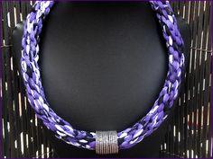 Collar trenzado en trapillo malva estampado, abalorio plateado. El collar se remata con terminales y  broche tipo mosquetón.