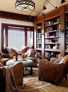I love how the four chairs encircle the round ottoman/table, and a window seat is off the the side. How To Design And Organize A Home Library - Hadley Court