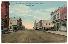 Vintage town view postcard showing Court Street, Looking West from 6th Street, Beatrice, Nebraska. Shows dirt street, people, businesses and buggy. Card is us