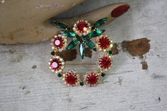 vintage rhinestone wreath brooch / 1960s holiday wreath pin / christmas wreath novelty brooch / red white green prong set rhinestone pin