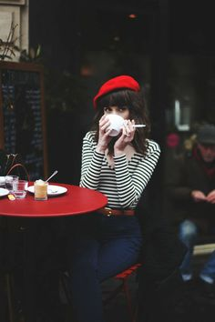 Paris-klassisches-Bild-Mädchen-Café-rote-französische-mütze-Kaffeetasse-Zigarette-roter-Tisch