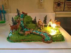 "Jerod's Deer Hunting Cake 13x9 cake for bottom layer. Cut a 9"" round into pieces for top two layers. Graham crackers for the tent..."