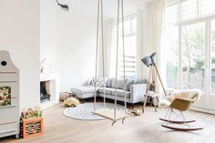 love this entire room... grey sectional, eames rocking chair + natural wood swing