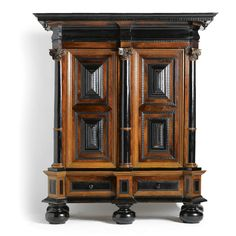 A DUTCH OAK, EBONY AND ROSEWOOD CUPBOARD OR 'KUSSENKAST' BAROQUE, SECOND HALF 17TH CENTURY  the protruding cornice above a pair of raised panelled doors, enclosing an interior with shelves and one drawer, flanked and divided by pilasters with Corithian capital, a long drawer below, sides with panels and pilaster, on large ball feet, alterations height 233cm., width 203cm., depth 81cm.
