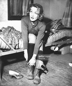 Actress Marlene Dietrich, 40, sporting Army sweater, knit cap & long wool underwear, sitting on bunk bed as she takes off her GI boots while preparing to don her sequined evening gown & gold pumps to perform onstage during USO show for a US Army