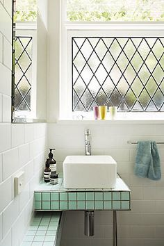 what a cute little bathroom! love the harlequin window panes and aqua tiles.