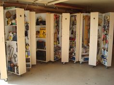 Garage diy wheeled storage cabinets open to reveal 3 storage areas Each outside door is pegboard on top and shelves at the bottom Center unit is walled up half way with places to hang on each side and above center divider is shelving