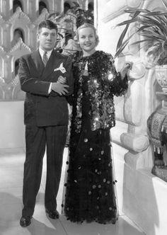 The average American woman of the mid-1930s may have fantasized about being Carole Lombard and having your wardrobe (onscreen, at least) designed by fashion maven Travis Banton (shown with Carole in Paramount).