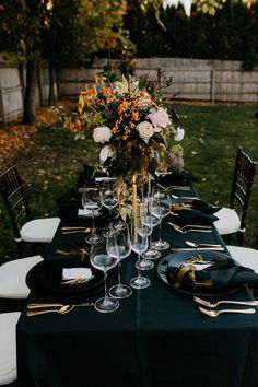 dark fall tablescape with oversized florals, black linens, gold silverware, and an autumn backyard backdrop.