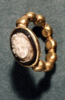 Gold finger-ring set with a sardonyx cameo engraved with a head of Medusa with wings in her hair and snaky locks.Roman, ca.1st century.