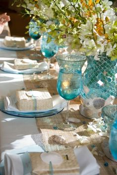 Aqua plates, goblets, votives along with the burlap table runners, lauhala favor boxes and seashells all set the tropical beachy mood. Photo: Jennifer Prater