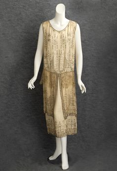 Beaded satin evening dress, c.1924. Made from ivory cream satin, the dress is lavishly embellished with faux pearls, silver beads, and silver-lined crystal beads.