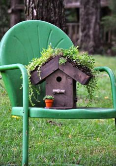 Süßes kleines Vogelhaus mit begrüntem Dach steht auf einem Stuhl