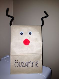 DIY Christmas Goodie Bag. Note to self: include a picture of Santa or Rudolph for the kids to colour; spruce up a brown paper bag with a sheet of printed wrapping paper & some ribbon