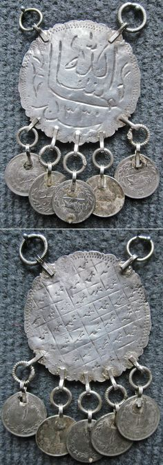 Front and reverse of a silver pendent with Iranian coins.  From (western?) Iran, early 20th century, possibly Kurdish. Ø disc: 48 mm.   Inscribed ('Inshallah' + maybe some other text) and dated H.1330 (1912 AD).  The inscription has a protective function, which makes the pendent a kind of amulet.  (Inv.n° müç061 - Kavak Costume Collection - Antwerpen/Belgium).