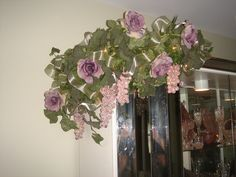 Garland with purple roses, ivy, lights and sage ribbon on the corner of a china cabinet