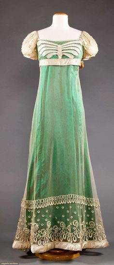 Cream silk and tulle gown with decorative cream satin bands, lace & embroidery to hem & bodice. Green satin underdress is a reproduction. c1820. American? Augusta Auctions.