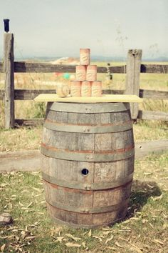 Set up a pyramid of cans on top of a barrel and see who can knock them all down.