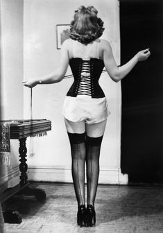 lady tightens her laces around early 20th century #corset #waisttraining #corsettraining #tightlacing