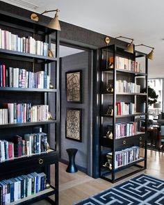 design by kemble interiors.  Black open bookcases on black wall with brass arm swing sconces above.