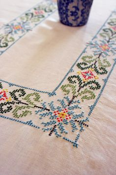 Large linen tablecloth, prettily hand embroidered with a cross stitch design. There are 10 napkins which are also embroidered with a motif and colour co-ordinated borders.    This is a lovely item and would make a lovely gift or wedding present.    Colour:  Cloth/Napkins: Off White  Embroidery: Dark Green, Pale Green, Dark Turquoise, Light Turquoise, Yellow, Coral, Brown    Size:  186cm x 131cm  73¼ x 51½    Condition:  Good vintage condition    All prices are standard post. If you requi...
