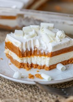 Pumpkin Lasagna - a delicious layered dessert with a Pumpkin Oreo crust, cream cheese layer, pumpkin pudding layer, and topped with cream and white chocolate curls. It's PHENOMENAL!