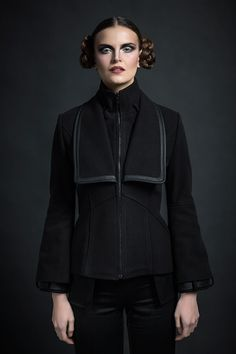 Chevalier Noir Jacket:   Buy it on https://www.roanneothman.com/p/60/chevalier-noir    A capital posture in the form of a warm wool mix, princess line jacket that fastens with a zip through the front. With slightly padded shoulders, it boasts an ultimate silhouette.    This jacket is distinct with a toned sculptural outline, created by an inner standing collar, topped with a lapel overlaid on the chest and bound with trimming all around. With a loop on each side of the inner collar, this…